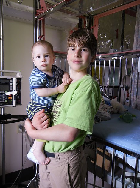 Enoch holding Apollo in the hospital.