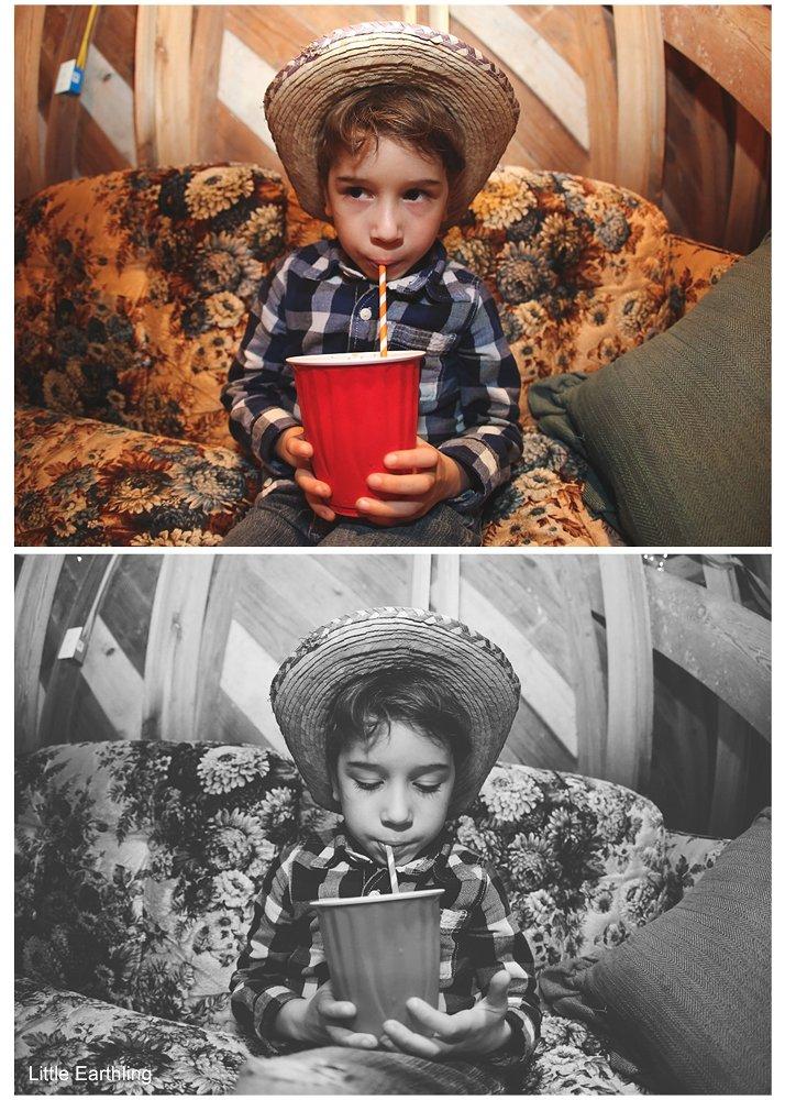 Little boy in big cowboy hat sipping a drink