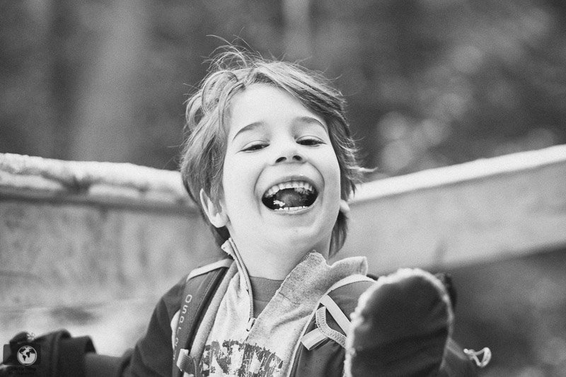black and white image of smiling boy eating snow
