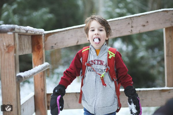 smiling boy with mouth full of snow