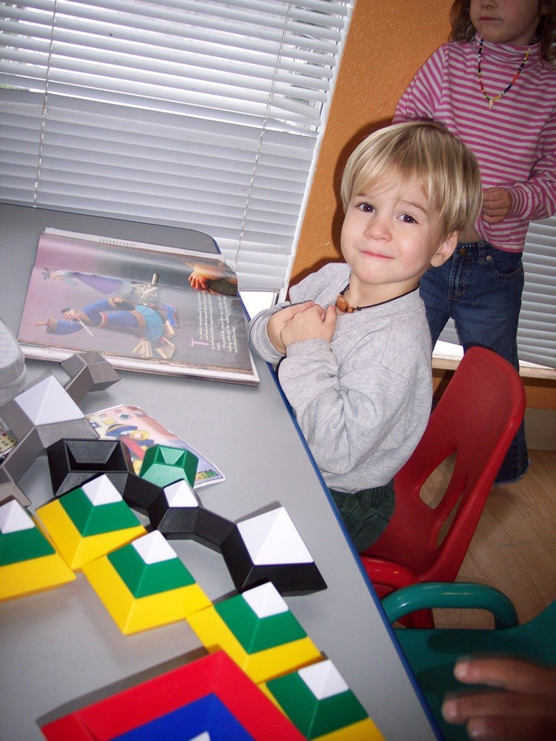 Two-year-old Hezekiah busy at work at our Lakeshore preschool table.