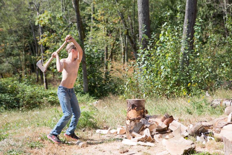 Boy chopping wood with ax