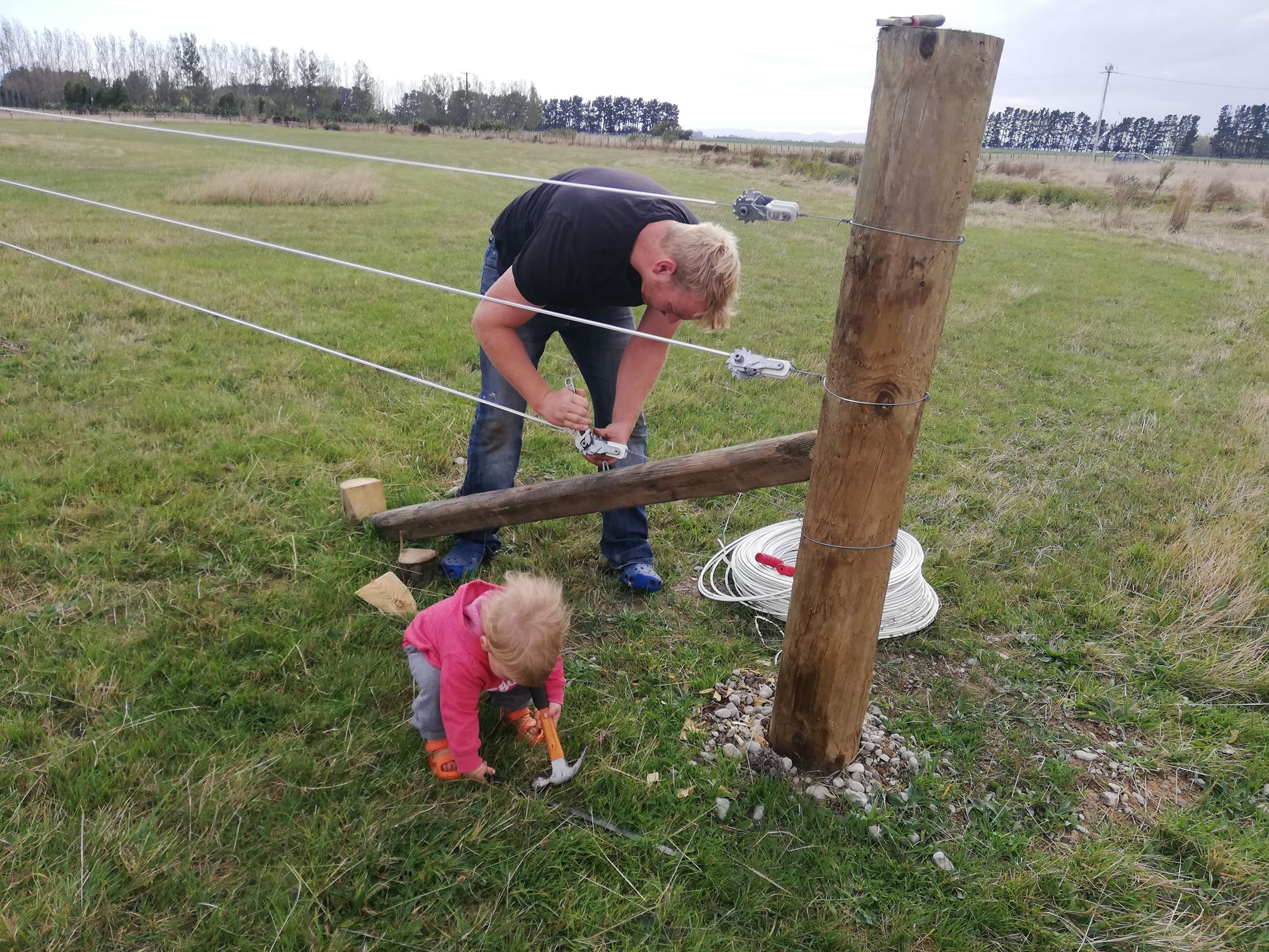 Sending digital photos is a great way to keep in touch with long-distance family. Ben and Percy build a fence together in New Zealand.