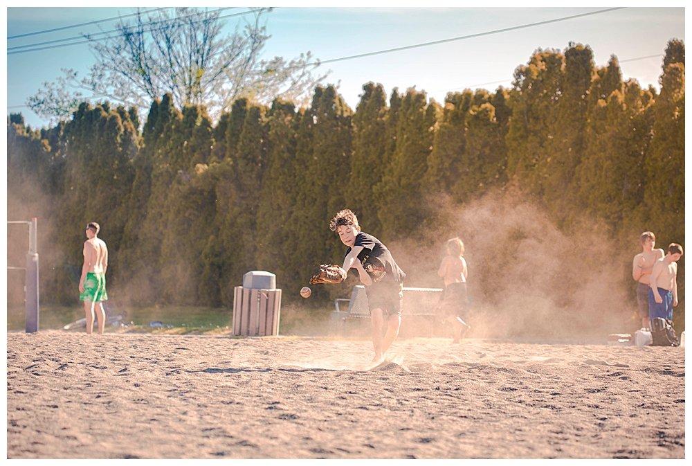 Dust stirred up as boy catches baseball. PNW photographer.