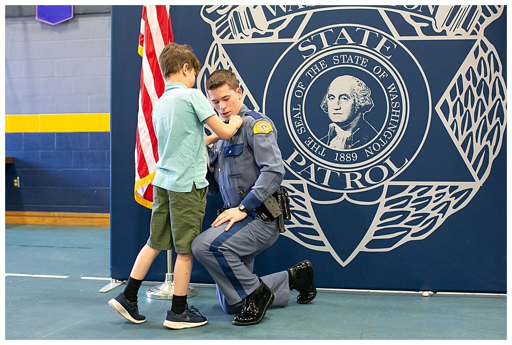 Apollo pinning badge on Judah at graduation. State trooper.
