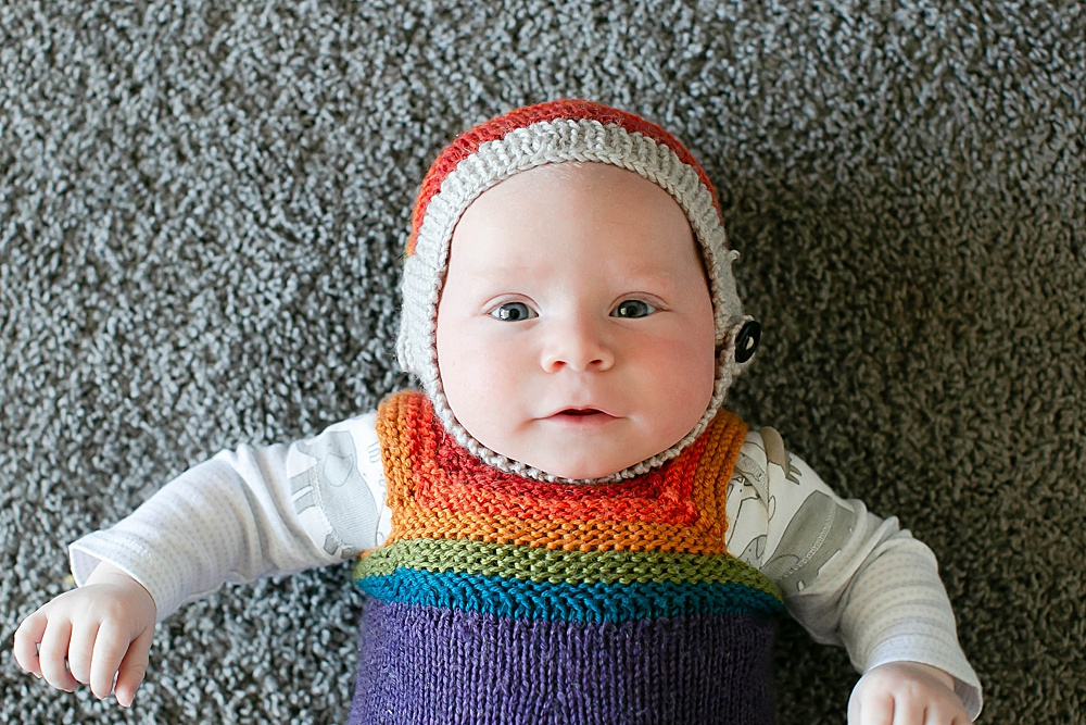 Abel two months in rainbow sweater and hat