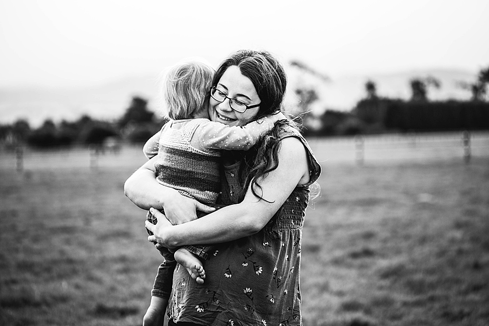 Black and white portrait of Percy hugging Adalia. 40 weeks pregnant.