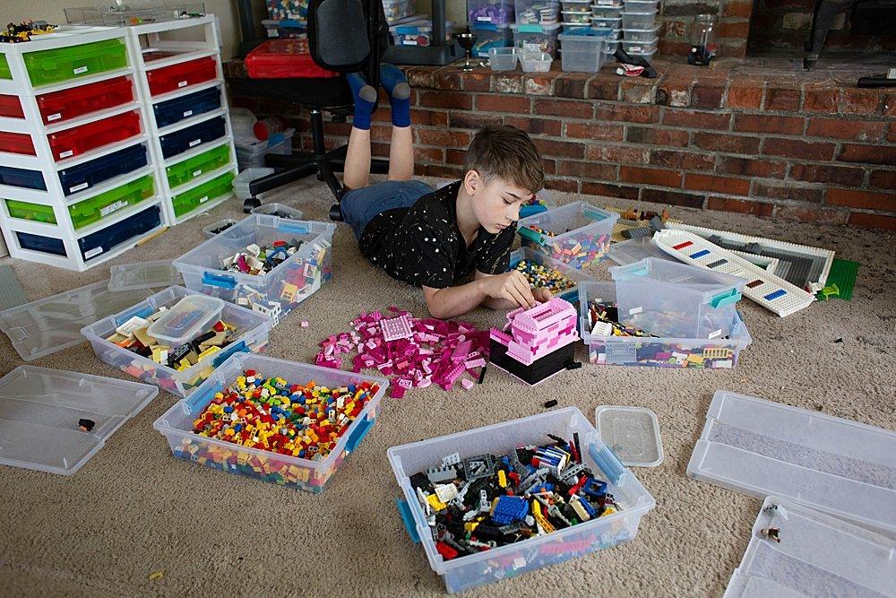 boy lying of floor playing with LEGO bricks