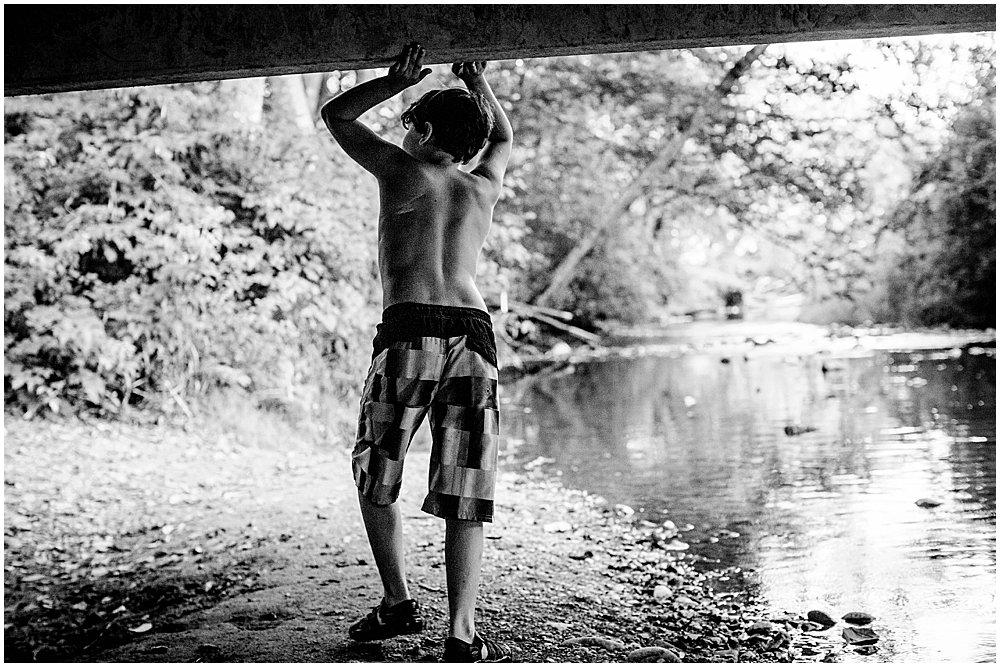 Black and white portrait of boy in creek. Apollo