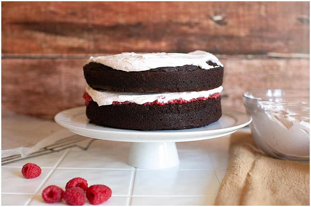 Chocolate cake with layers of raspberries and whipped cream.