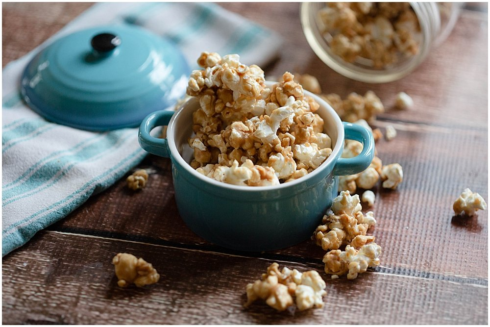 Popcorn in bowl on wooden table.