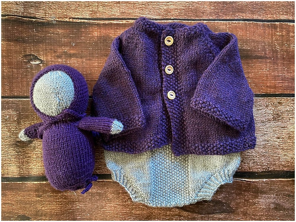 hand knit baby cardigan, romper, and doll.
