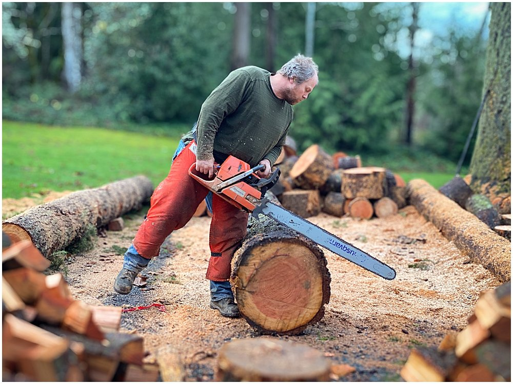 Chuck cutting wood with chainsaw.